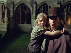 Hugh Jackman as Jean Valjean carrying young Cosette