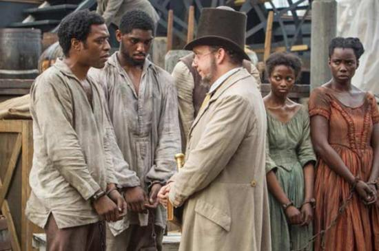 Solomon and fellow enslaved meet slave trader Mr. Freeman (Paul Giamatti)